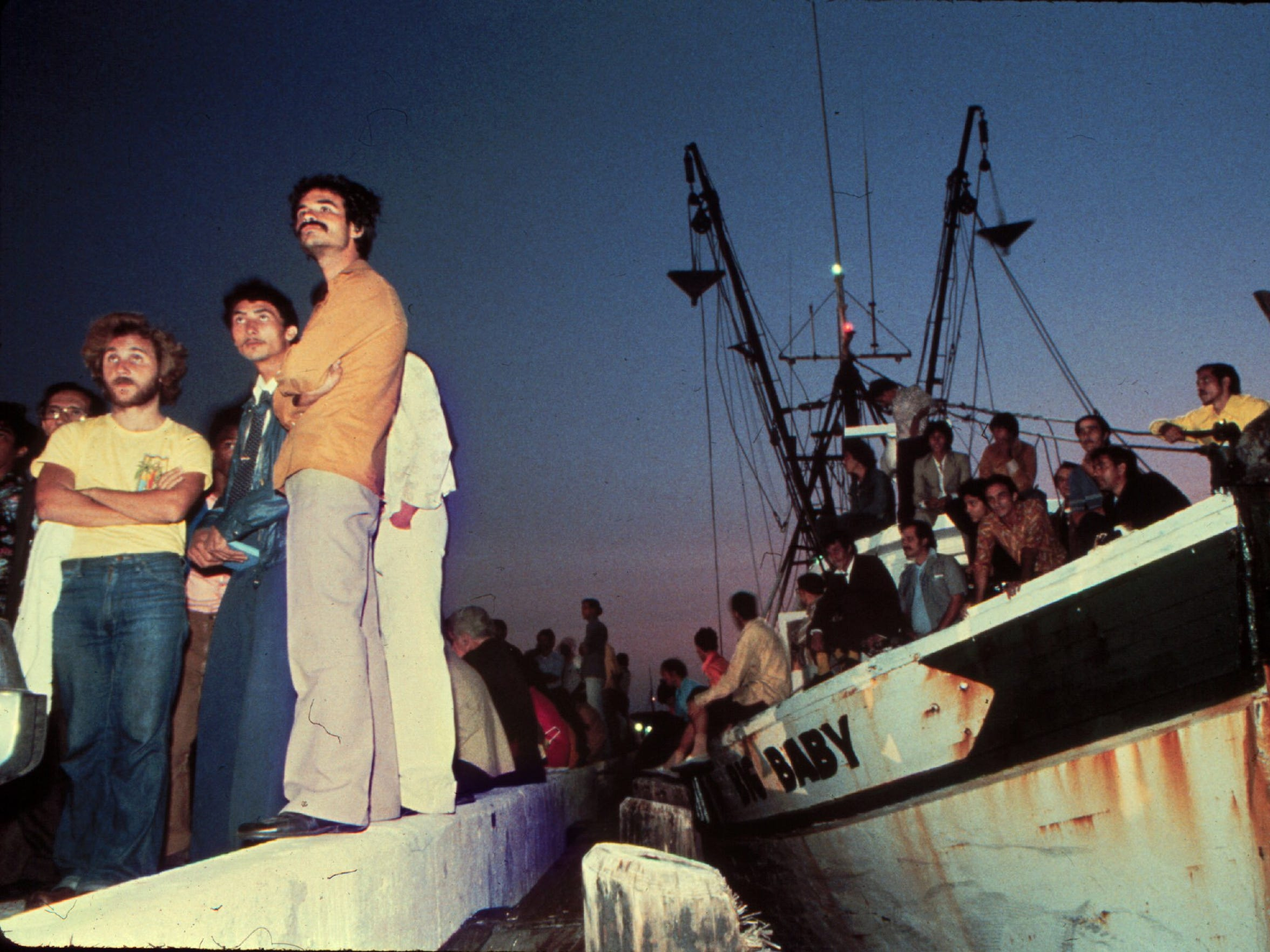 April 23, 1980: Mariel refugees savor the new dawn over Key West Harbor and their first taste of freedom.