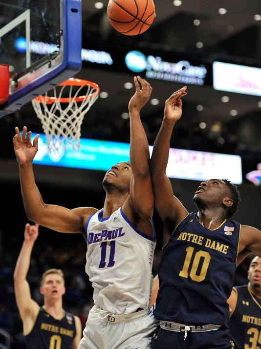 DePaul's Eli Cain (11) battles Notre Dame's Temple Gibbs (10) for a rebound during the second half of an NCAA college basketball game Saturday, Nov. 11, 2017, in Chicago. Notre Dame won 72-58. (AP Photo/Paul Beaty)