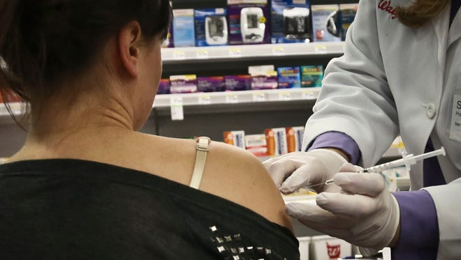 Pharmacist Stacia Woodcock, a pharmacy manager for Walgreens in New York, administers a flu vaccine on site, Monday, Jan. 14, 2013.