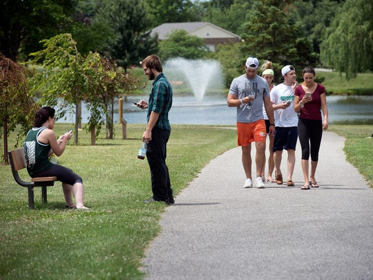 Groups of friends walk around Cousler Park in Manchester