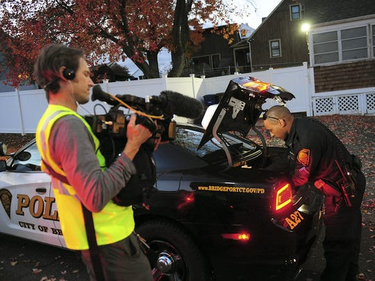 "In this Nov. 3, 2016 photo, a crew from the television program ""Live PD,"" a reality show by the A&E Network, records an officer from the Bridgeport Police Department while on patrol in Bridgeport, Conn."