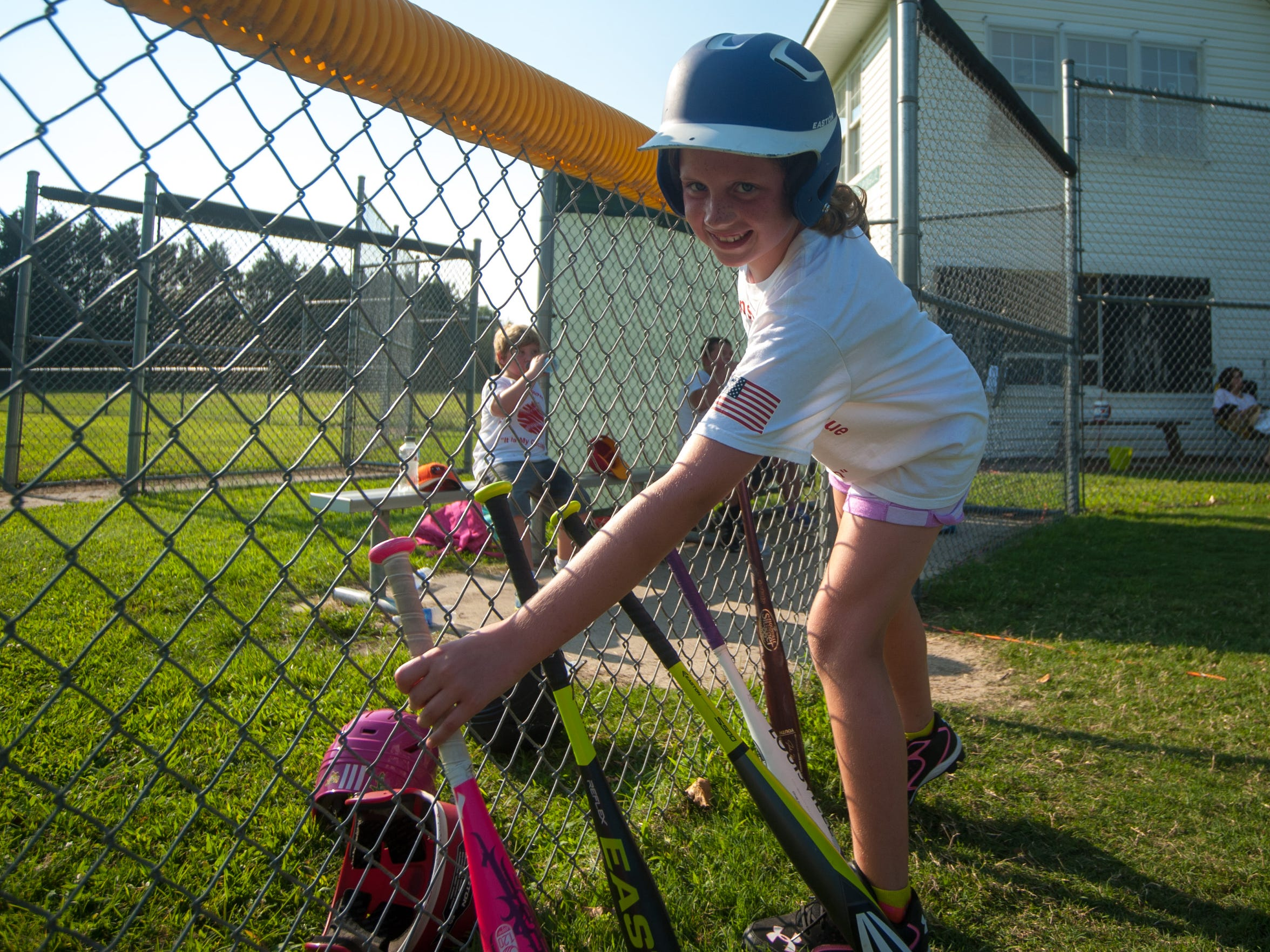 A Tom Brown Rookie Leaguer grabs her bat on Monday
