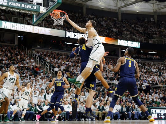 Gavin Schilling dunks over Michigan's Isaiah Livers (4) and Jon Teske in the first half on Saturday.