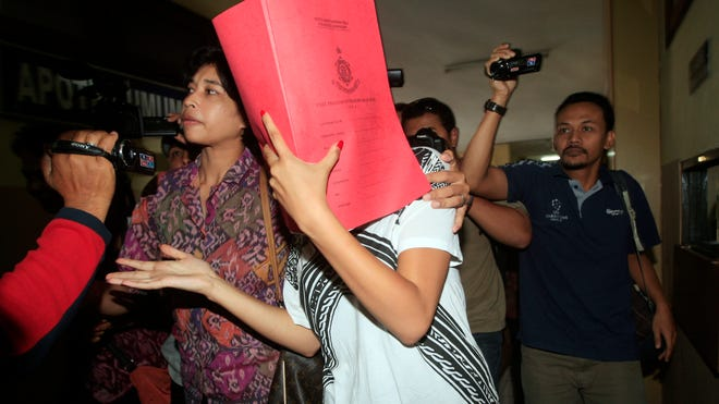 Heather Mack, covering her face, is led to a hospital for a medical check by Indonesian police officers in connection to the death of her mother, Sheila von Wiese-Mack, in Bali, Indonesia, on Aug. 15, 2014.