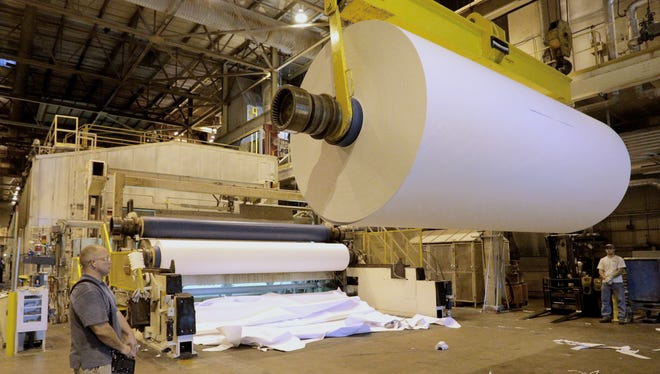 Chad Stich uses a portable electronic controller to remove a roll of paper at Domtar's Rothschild Mill. The rolled paper is taken off the paper machine and will be replaced by an empty roller which will accept more paper.