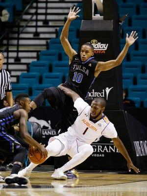 Auburn guard KT Harrell (1) falls into Tulsa guard James Woodard (10) during the first half of an NCAA college basketball game Monday, Nov. 24, 2014, in Las Vegas. (AP Photo/John Locher)