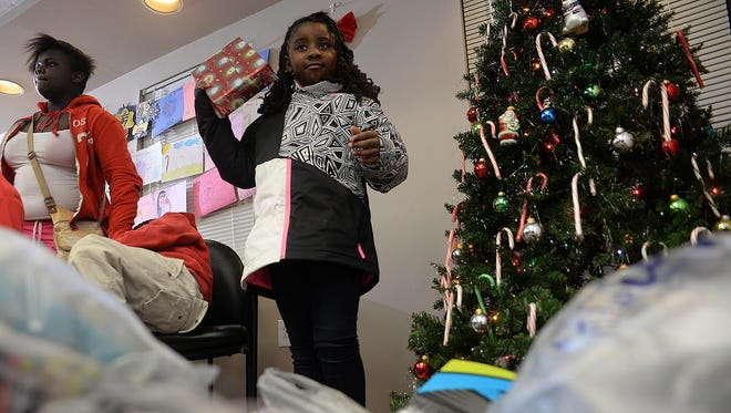 Peytan Satterfield, 7, of Bridgeton, shakes a gift box Wednesday, hoping to receive Shopkins toys at the NIA Amity Heights Apartments Christmas party, Dec. 16 in Bridgeton.  Presents for all the children in attendance were donated by Fairton Christian Center.