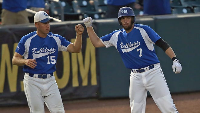 Van Meter head coach Mike Kennedy, left, gives a fist bump to Brandon Brittain at third base against Beckman's (Dyersville) in the Class 2A semifinal game at the 2014 state baseball tournament at Principal Park in Des Moines on July 31, 2014.