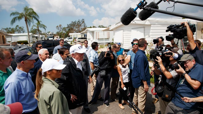 President Donald Trump talks with reporters as he tours Naples Estates, a neighborhood impacted by Hurricane Irma, Thursday, Sept. 14, 2017, in Naples, Fla.  Behind the president from front to back are, first lady Melania Trump, Gov. Rick Scott, R-Fla., Vice President Mike Pence and Sen. Marco Rubio, R-Fla.  (AP Photo/Evan Vucci)