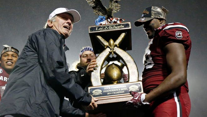 South Carolina head coach Steve Spurrier, left, and South Carolina linebacker Jonathan Walton (28) hold the Independence Bowl trophy after they defeated Miami 24-21 in Shreveport, La., Saturday.