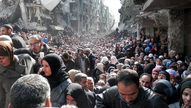This picture taken on Jan. 31, 2014, and released by the United Nations Relief and Works Agency for Palestine Refugees in the Near East (UNRWA), shows residents of the besieged Palestinian camp of Yarmouk, queuing to receive food supplies, in Damascus, Syria. A United Nations official is calling on warring sides in Syria to allow aid workers to resume distribution of food and medicine in a besieged Palestinian district of Damascus. The call comes as U.N. Secretary General Ban Ki-Moon urged Syrian government to authorize more humanitarian staff to work inside the country, devastated by its 3-year-old conflict.
