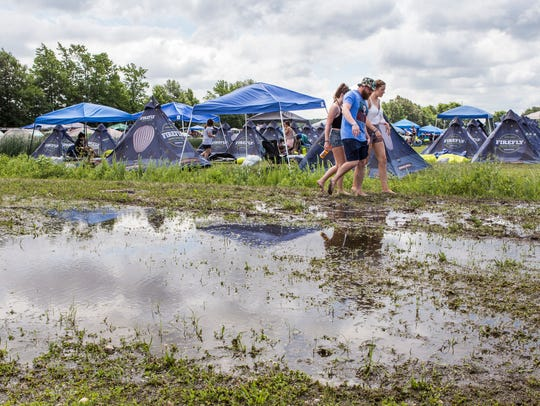 Campers walk through flooded ground in the Westwoods