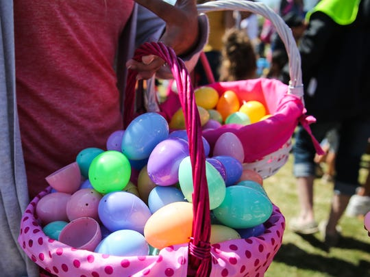 A parent carries baskets filled with eggs at Easter Fest Saturday, March 31, 2018, at Texas Bank Sports Complex.