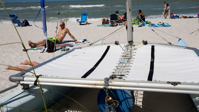 A chained-up Hobie Cat sits near residents and tourists as they soak up the sun at the Central Avenue access point Wednesday, April 11, 2018, in Naples. The sailboat is a part of the city's Boats on the Beach program that allows Naples residents to rent out public beach space to store nonmotorized vessels at specific locations on the beach. The city is considering ending the program.