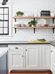 Interior designer Kristina Crestin uses fresh plants to add color to a monochrome kitchen.