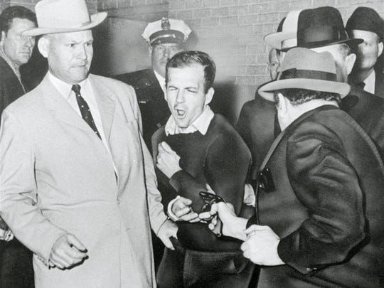 Detective Jim Leavelle is at left when Lee Harvey Oswald, assassin of President John F. Kennedy, reacts as Dallas night club owner Jack Ruby, foreground, shoots at him from point blank range in a corridor of Dallas police headquarters, Nov. 24, 1963.