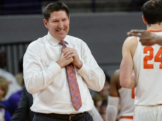 Clemson coach Brad Brownell smiles at a referee after