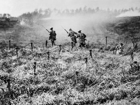 U.S. troops of the 107th Regiment Infantry, 27th Division, advance on a path through a barbed wire entanglement near Beauqueanes, Somme, France in this Sept. 13, 1918 file photo (AP Photo/U.S. Army Signal Corps, File)