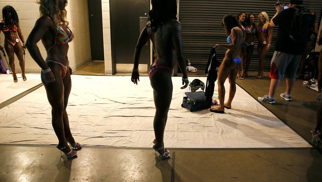 Michelle Reynolds-Madden 40, of Fort Thomas, left, and Angi Lampkin, 44, of Florence, practice their poses before taking the stage in theKentucky Derby Festival Championshipsof bodybuilding at the The Kentucky International Convention Center in Louisville Saturday April 30, 2016. This is the first time the two have competed in a bodybuilding show.
