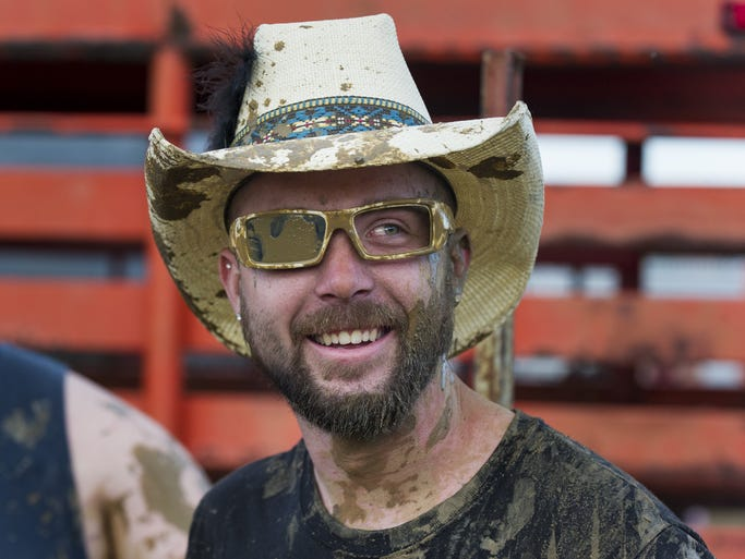 Eric Smith, of Franklin, lost his sunglasses in the ring while wrestling a pig with his teammates. Once found, the mud-covered glasses were minus one lens. The Johnson County Fair offers this year's guests with a variety of activities. Thursday, July 17, 2014, featured a hog wrestling event in the fans in the grandstands.