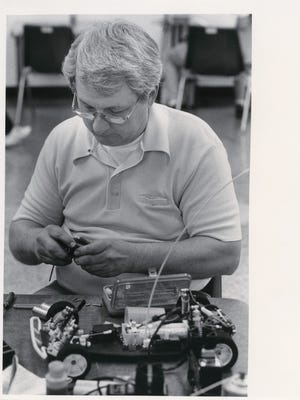 Mark Johnston does some last minute tinkering on his remote control car's electric motor at the SARCAR off-road season championship race in March of 1986.