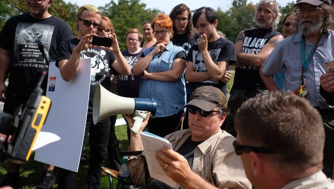 Activist Chris Irwin, who organizes the protest against the white supremacists, is told he can't use the megaphone because of noise complaints during a Stormfront summit in Crossville on Saturday, Sept. 30, 2017.
