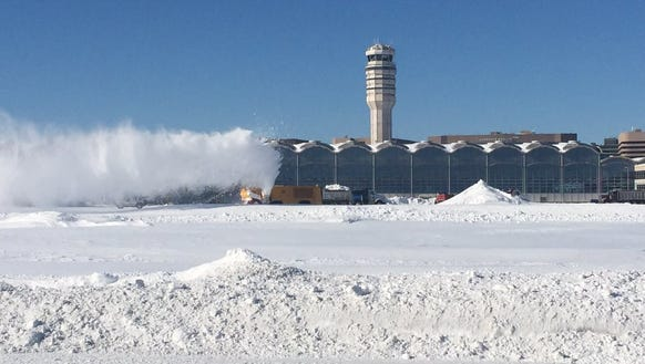 Airport crews work to clear more than foot of snow