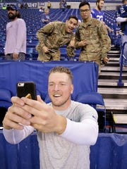 Pat McAfee takes a selfie with two members of the U.S. Armed forces before the Colts faced the Kansas City Chiefs on Oct. 30 at Lucas Oil Stadium.