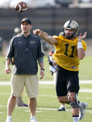 New quarterbacks coach Tim Lester, background left, watches quarterback David Blough in drills during spring football practice Tuesday, March 8, 2016, at Purdue University.