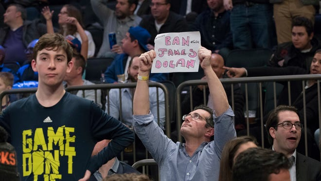 """A New York Knicks fan holds a """"Ban James Dolan"""" sign during Friday's game at Madison Square Garden"""