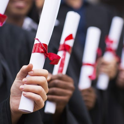 Group of graduates holding diploma - Generic Images