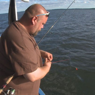 An angler on a Mille Lacs Lake launch baits his jig