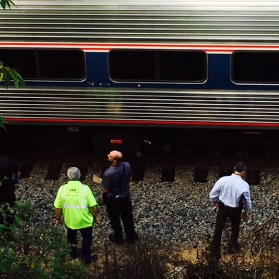Accident investigators look at a train that collided