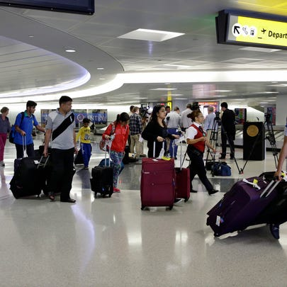 Passengers pull their luggage at Newark Liberty Airport