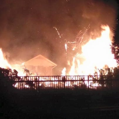 A brush fire spread to two nearby homes early Saturday