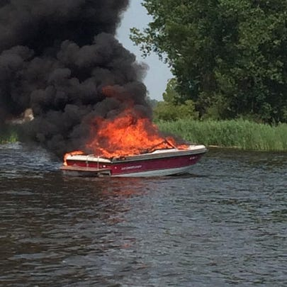 A burning boat drifts toward shore late Sunday afternoon