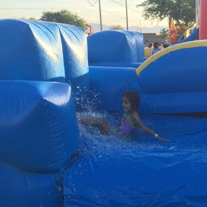 A child enjoys a water slide at the Red, White and