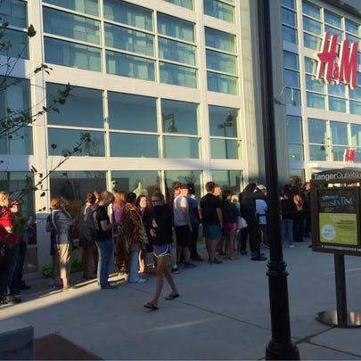 Shoppers wait to get into the H&M at Tanger Outlets