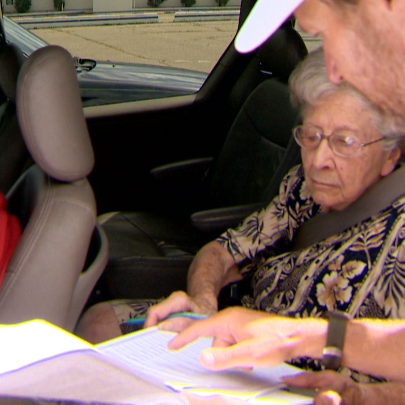 Protesters gets a passer-by to sign a recall petition.
