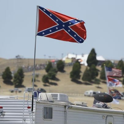 A Confederate flag flies atop an RV in a campground