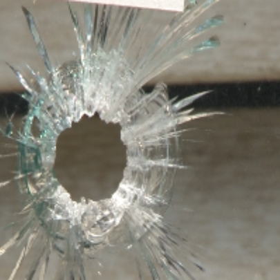 A bullet hole in a window of a home hit during a recent