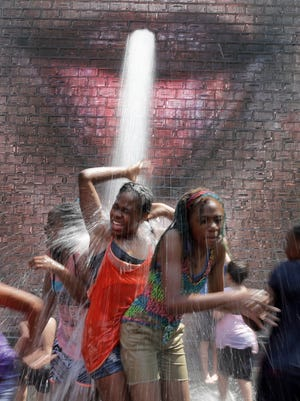 Girls cool themselves from a stream of water at the Crown Fountain in Chicago's Millennium Park, June 15, 2018, in Chicago. The National Weather service in Chicago has issued a excessive heat watch for Saturday through Monday for the area.