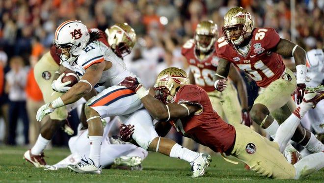 Auburn Tigers running back Tre Mason is tackled by Florida State linebacker Christian Jones.