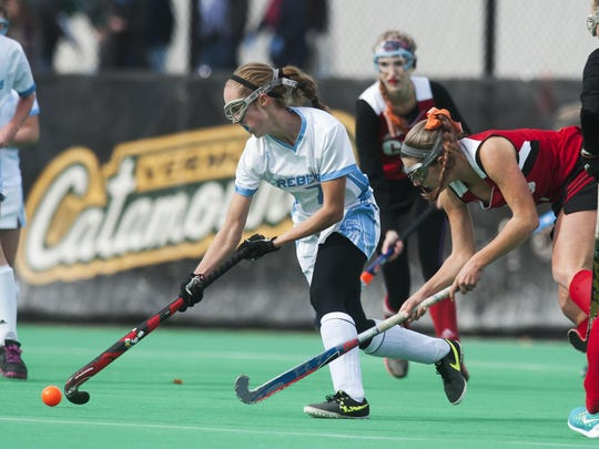 South Burlington's Olivia Dickinson, middle, runs down the field with the ball during year's Division I state championship game.