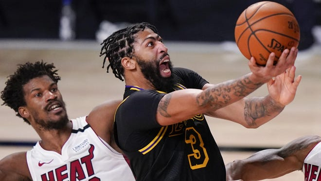 Los Angeles Lakers forward Anthony Davis shoots between Miami Heat forward Jimmy Butler, left, and guard Andre Iguodala during the second half in Game 5 of basketball's NBA Finals Friday, Oct. 9, 2020, in Lake Buena Vista, Fla.