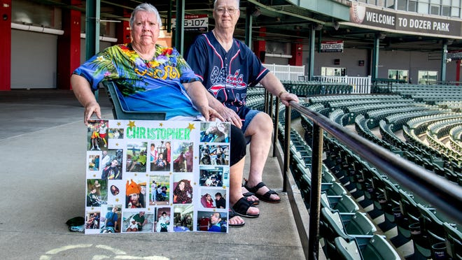 Barb and Joe Bolander sit in their seats with a display of photos of their son Chris, 36, at Dozer Park in Peoria. Chris, whom they adopted at the age of 2, was wheelchair-bound with cerebral palsy and a huge fan of the Peoria Chiefs. He died recently and his parents scattered some of his ashes near the pitcher's mound.