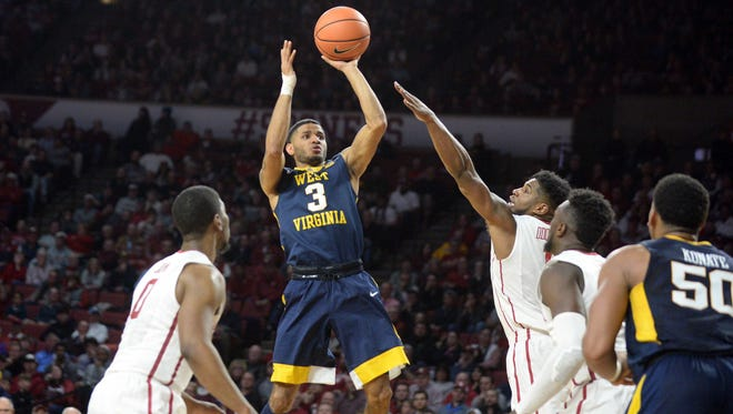 West Virginia guard James Bolden (3) puts up a shot between a trio of Oklahoma defenders during the first half.