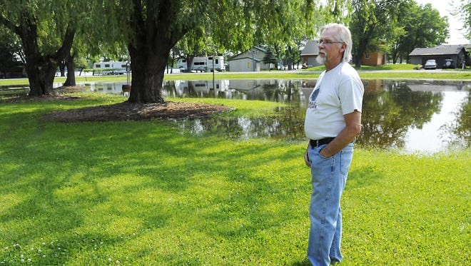 Homeowner Bob Gray stands outside his property on Two Rivers Road in Avon on Monday. A pond has began to form outside of his house due to water levels rising from Two Rivers Lake.
