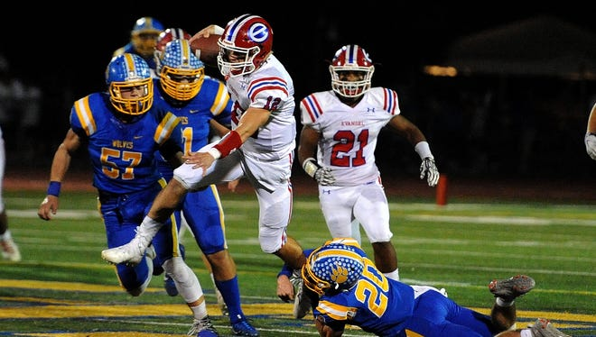 Evangel quarterback Connor Curry tries to sidestep a St. Paul defender Friday night in the Division I state playoff contest.