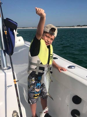 Alec Arnold with two Spanish Mackerels he caught at once while fishing with his dad, Captain Andy Arnold, this past week.